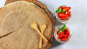 Homemade, exquisite dessert tiramisu in glasses decorated with strawberry, mint, On a wooden stump. Authentic lifestyle image. cop royalty free stock photography