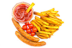 Homemade fast food, portion of french fries, ketchup, grilled sausages and cherry tomato isolated on white background. Stock Image