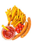 Homemade fast food, portion of french fries, ketchup, grilled sausages and cherry tomato isolated on white background. Stock Photo