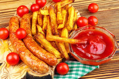 Homemade fast food, portion of french fries, ketchup, grilled sausages and cherry tomato on wooden board. Stock Images