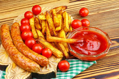 Homemade fast food, portion of french fries, ketchup, grilled sausages and cherry tomato on wooden board. Royalty Free Stock Images