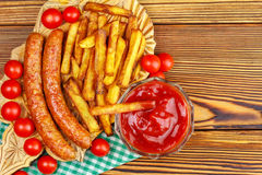 Homemade fast food, portion of french fries, ketchup, grilled sausages and cherry tomato on wooden board. Stock Photo