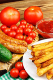 Homemade fast food, portion of french fries, ketchup, grilled sausages and cherry tomato on wooden board. Royalty Free Stock Photography