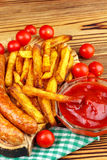 Homemade fast food, portion of french fries, ketchup, grilled sausages and cherry tomato on wooden board. Stock Image