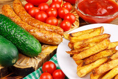 Homemade fast food, portion of french fries, ketchup, grilled sausages and cherry tomato on wooden board. Royalty Free Stock Photo