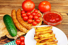 Homemade fast food, portion of french fries, ketchup, grilled sausages and cherry tomato on wooden board. Royalty Free Stock Photos