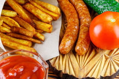 Homemade fast food, portion of french fries, ketchup, grilled sausages, tomato, cucumber on wooden board. Royalty Free Stock Photos