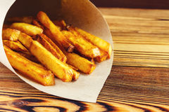Homemade fast food portion of french fries in paper bag on wood table Royalty Free Stock Photos