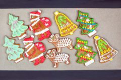 Homemade festive Shaped gingerbreads on cooking paper. Homemade festive different Shape gingerbreads on cooking paper. Festive indoors closeup multicolored Stock Photos