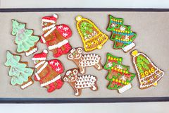 Homemade festive Shaped gingerbreads on cooking paper. Homemade festive different Shape gingerbreads on cooking paper. Festive indoors closeup multicolored Royalty Free Stock Images