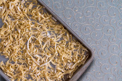 Homemade fettuccine pasta drying on a metal tray. Overhead view of fresh homemade fettuccine pasta noodles drying on a metal tray placed on a decorative royalty free stock image