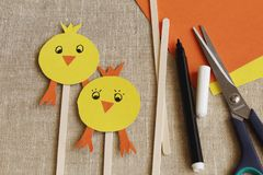 Handmade. Yellow stylized funny chickens, scissors, colored paper, wooden sticks, black felt-tip pen on rough burlap royalty free stock photography