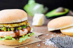 Homemade fish burger with salmon, avocado and pineapple.Close up Stock Images