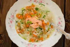Homemade fish soup with rice and carrot on wooden background Stock Images