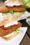 Homemade Fishburger on wooden background Stock Photography