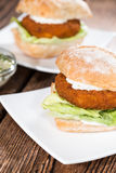 Homemade Fishburger on wooden background Royalty Free Stock Photography