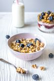 Homemade fitness granola with yoghurt and berries on white kitch. Homemade fitness granola with yoghurt and blueberries on white kitchen table background royalty free stock image