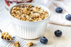 Homemade fitness granola with yoghurt and berries on white kitchen background. Homemade fitness granola with yoghurt and blueberries on white kitchen table royalty free stock photos