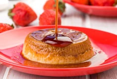 Homemade flan with strawberries, on red Royalty Free Stock Photos