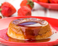 Homemade flan with strawberries, on red Stock Images