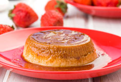 Homemade flan with strawberries, on red Royalty Free Stock Image