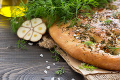 Homemade focaccia with dill, garlic and olive oil on a wooden ta Stock Photos