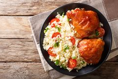 Homemade food: baked chicken thighs with garnish of rice close u. Homemade food: baked chicken thighs with garnish of rice on a plate close up. Horizontal top royalty free stock images