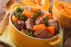 Homemade Food: Beef stew with pumpkin closeup in the yellow pot. Royalty Free Stock Image