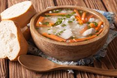 Homemade Food: Chicken rice soup in a wooden bowl. Horizontal Stock Image