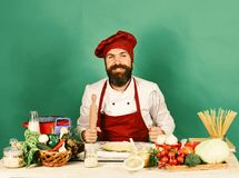 Homemade food concept. Man with beard sits by countertop. On green background. Cook with smiling face in burgundy uniform holds rolling pin. Chef with pasta stock images