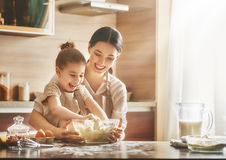 Homemade food and little helper. Happy loving family are preparing bakery together. Mother and child daughter girl are cooking cookies and having fun in the stock photo