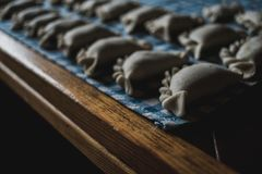 Making traditional Polish pierogi. Closeup of dumplings laying on a kitchen cloth. Homemade food - making traditional Polish pierogi. Closeup of dumplings stock photo
