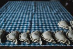 Making traditional Polish pierogi. Dumplings laying on a kitchen cloth. Homemade food - making traditional Polish pierogi. Dumplings laying on a kitchen cloth royalty free stock images