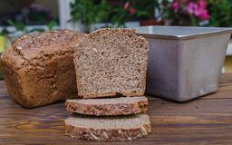 Homemade black bread with some bread slices lying on wooden surface Royalty Free Stock Photography