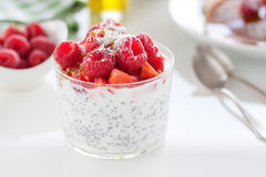 Homemade fresh chia pudding with yogurt, strawberry, raspberry, nuts and coconut in a glass. On a white table, closeup Stock Photo