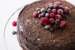 Homemade fresh chocolate birthday cake with organic frozen berries and chips on the top. Crystal plate wiht a nice cake Royalty Free Stock Photography