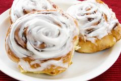 Homemade Cinnamon Sticky Buns on a White Plate. Homemade fresh cinnamon sticky bun rolls with white glazed icing served on white dishware with a red placemat in Royalty Free Stock Photos