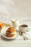 Homemade fresh cream puff with whipped cream and apricots, cup of coffee and milk jug. Royalty Free Stock Photo
