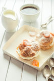 Homemade fresh cream puff with whipped cream and apricots powdered sugar on top, cup of coffee and milk jug. Toning. Stock Photo
