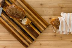 Homemade fresh crusty wholewheat bread. With one loaf on a decorative bread board and a second wrapped in a cloth viewed from above on a wooden table Royalty Free Stock Photos