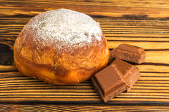 Homemade fresh donut sprinkled with powdered sugar and cubes of chocolate on wooden table Stock Photo