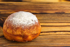Homemade fresh donut sprinkled with powdered sugar on wooden table with space for text Royalty Free Stock Photo
