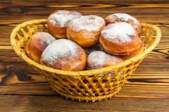 Homemade fresh donuts sprinkled with powdered sugar in wicker basket on wooden table Stock Photography