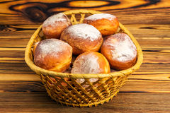 Homemade fresh donuts sprinkled with powdered sugar in wicker basket on wooden table Royalty Free Stock Images