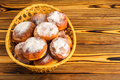 Homemade fresh donuts sprinkled with powdered sugar in wicker basket on wooden table, space for text Stock Photography