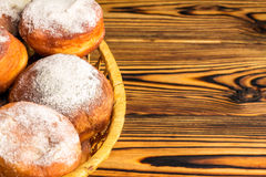 Homemade fresh donuts sprinkled with powdered sugar in wicker basket on wooden table, space for text Royalty Free Stock Images