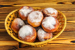 Homemade fresh donuts sprinkled with powdered sugar in wicker basket on wooden table, top view Stock Image