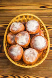 Homemade fresh donuts sprinkled with powdered sugar in wicker basket on wooden table, top view Royalty Free Stock Image