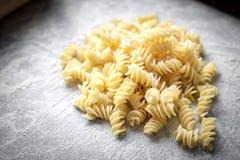 Homemade fresh handmade pasta with flour. Homemade fresh pasta and kitchen table with flour. Hand made fusilli closely stock photos