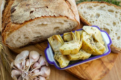 Homemade fresh italian bread and artichokes in brine with spices Royalty Free Stock Image